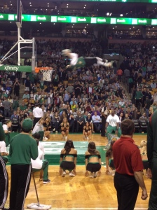 Lucky the Leprechaun, the Celtics' mascot who is wearing a festive St. Patrick's Day outfit, flies through the air to get a slam dunk.